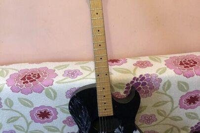 Гітара чорного кольору з білими візерунками з чохлом
