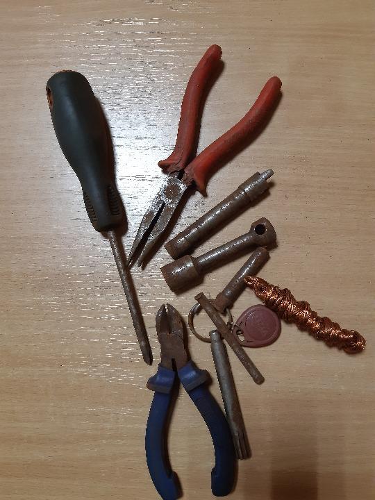 Чотири ключа до гвинтових замків, хрестоподібна викрутка, кусачки, плоскогубці, жмут мідної проволоки