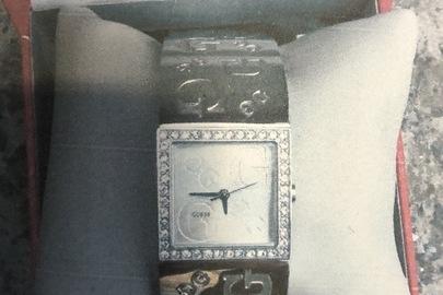 Годинник наручний, жіночий електричний, з механічною індикацією в корпусі та з браслетом з недорогоцінного металу білого кольору. Напис на циферблаті GUESS