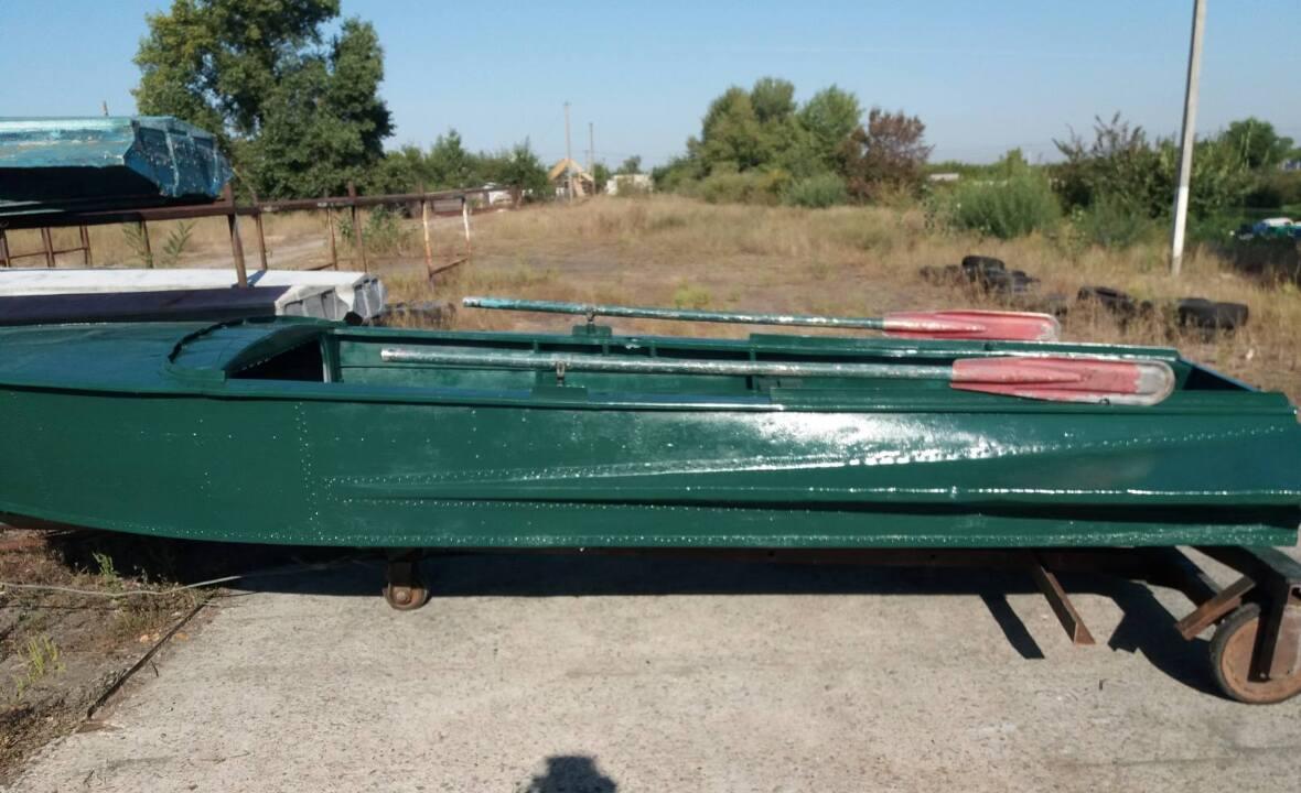 Човен зеленого кольору та два  весла